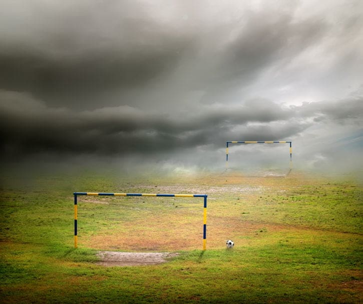 Football field, football goal, deflated ball and cloudy sky