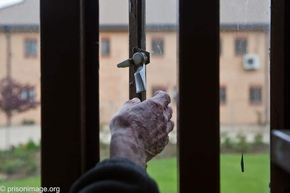 Older prisoner at his cell window