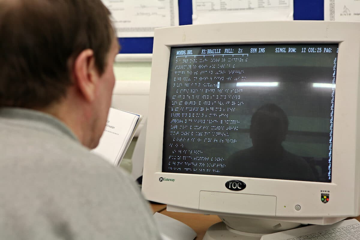 A visually impaired prisoner using a computer adapted for braille