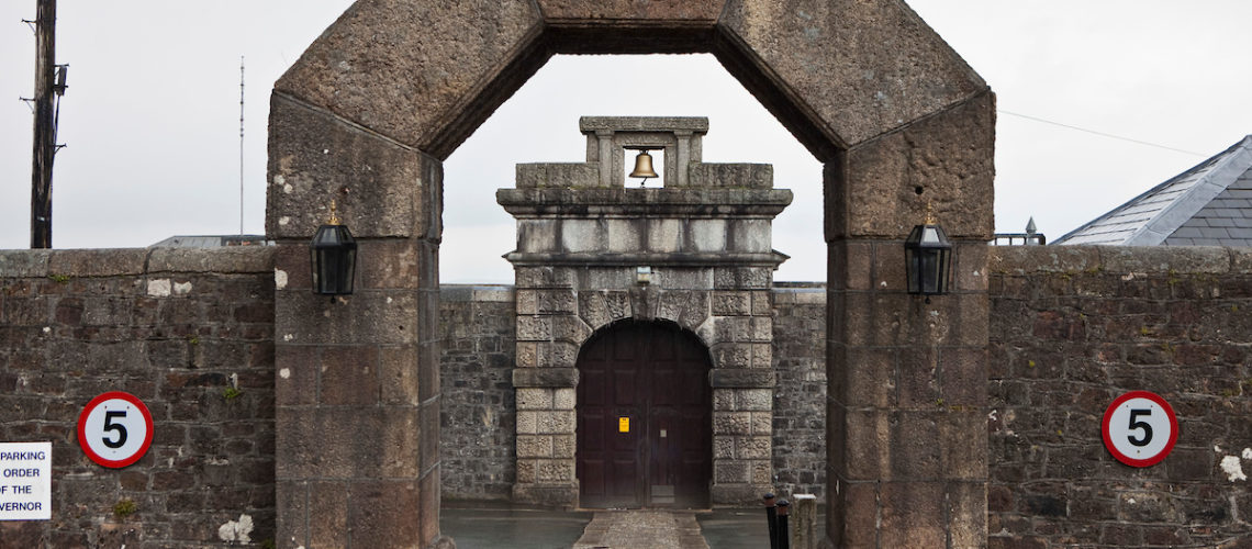 The main gates of HMP Dartmoor. Written atop the stone arch is Parcere Subjectis, a widely renowned Latin quote, meaning: To spare the vanquished. Princetown, Devon, United Kingdom.  Built in 1809, Dartmoor prison held French and American prisoners of war. It became a criminal prison from 1850. Most of the buildings date from the late 19th century but three wings have recently been fully refurbished. Dartmoor is now a Category C training prison.