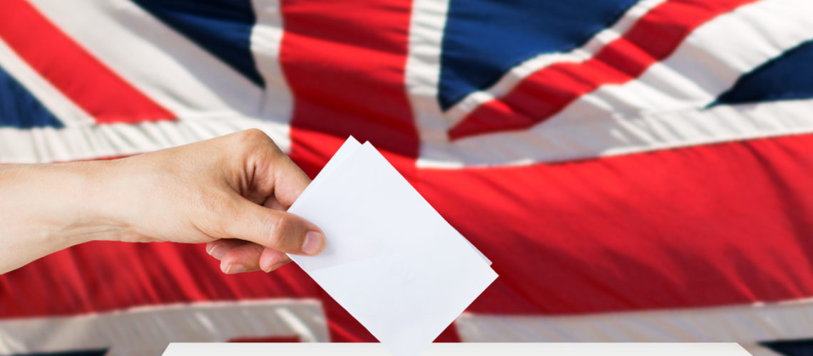 voting, civil rights and people concept - male hand putting his vote into ballot box on election over british flag background