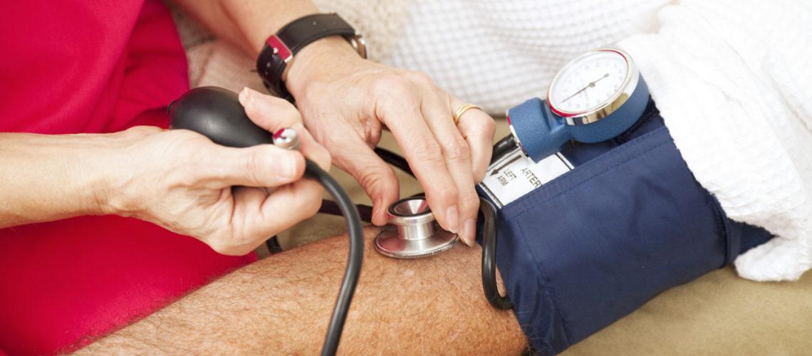Nurse taking a patient's blood pressure using a sphygmomanometer.  Closeup view.