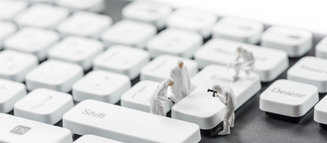 Group of miniature criminalists inspecting computer keyboard.  Cybercrime concept. Macro photo