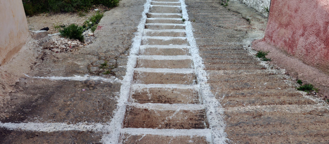 Narrow sloped alley with steps painted white. Greek mountain village old footpath.