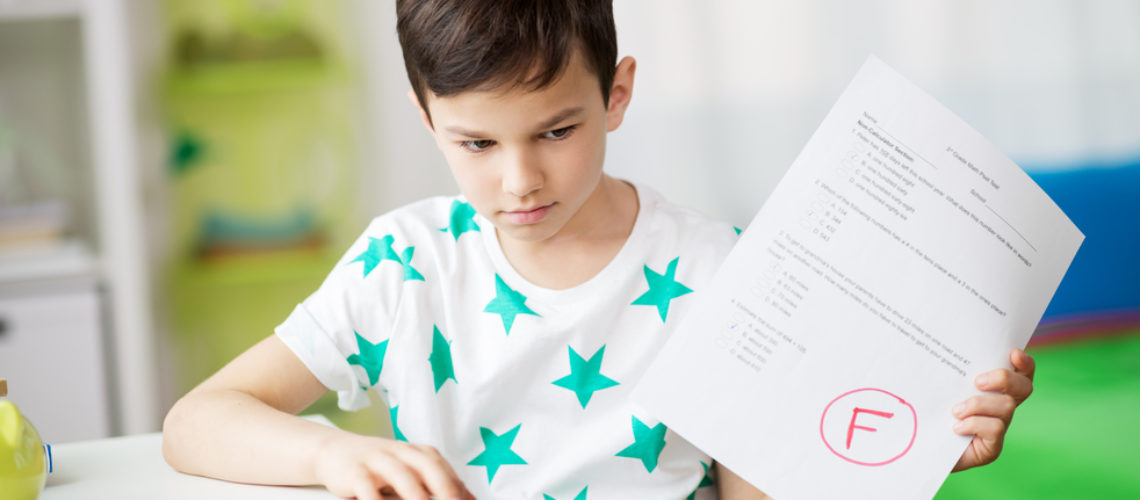 childhood, education and people concept - sad boy holding school test with f grade