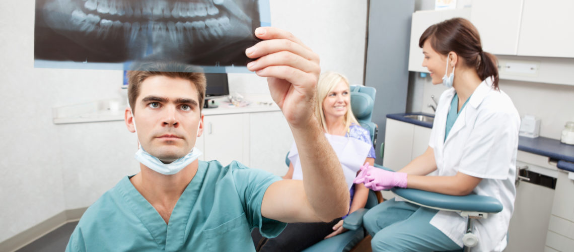 Radiodentist checking x-ray with assistant and patient having conversation in the background
