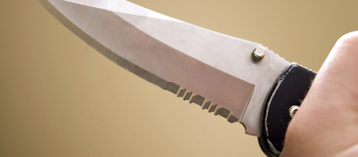Closeup of a hand gripping a dangerous knife with a sharp blade.