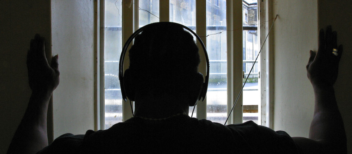 A prisoner in his cell listens on headphones to Radio Wanno, the prisons community radio station. HMP Wandsworth, London, United Kingdom