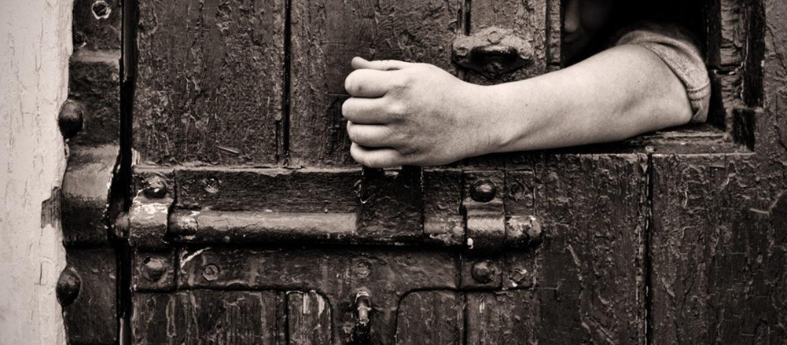 escape arm reaches through jail window to open the door