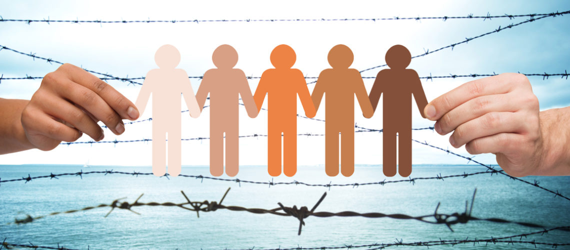 crime, imprisonment, refugee and humanity concept - multiracial couple hands holding chain of paper people pictogram over sea and barb wire background