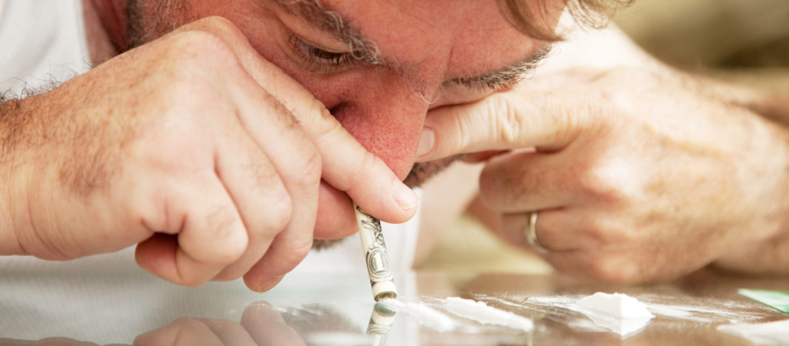 Middle-aged man using a rolled up dollar bill to snort cocaine off a glass coffee table.  **Dramatization - no illegal drugs were used in the creation of this photo**