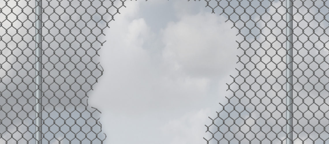 Thinking freedom and personal escape concept as a chain link fence with a hole shaped as a human head as motivation symbol or open mind psychological success metaphor.