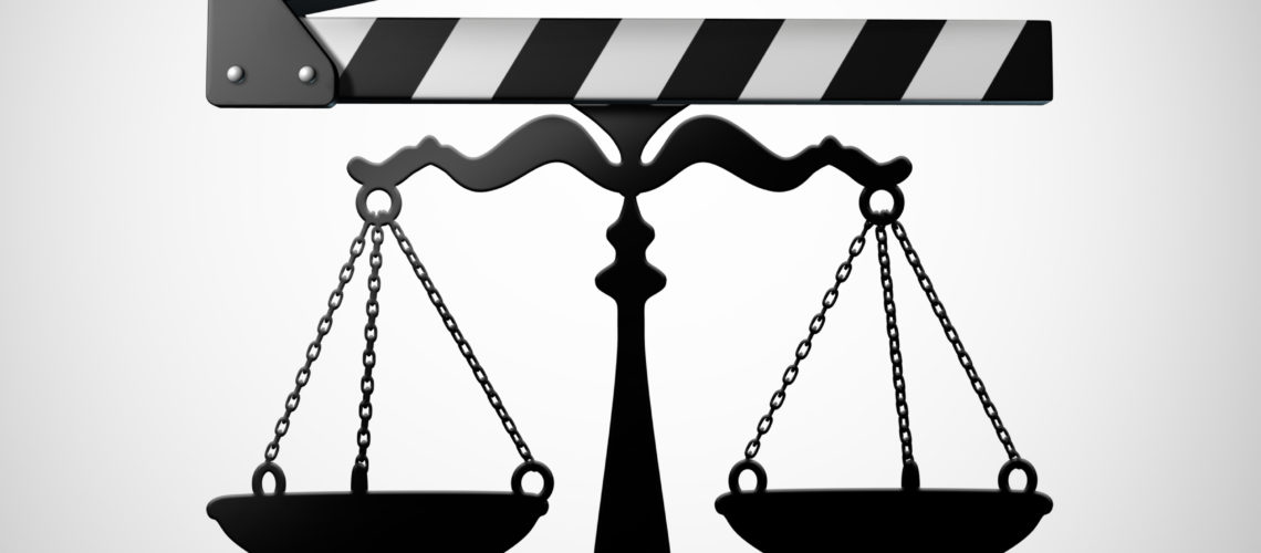 Entertainment law and media justice or TV and movie contract negotiation as a film industry slateboard or film slate shaped as a justice scale as a 3D render.