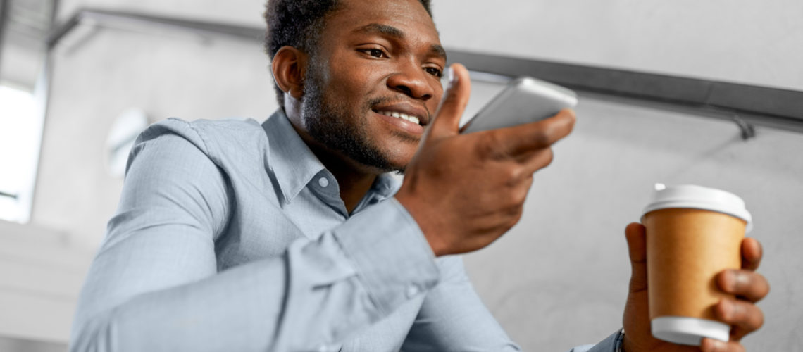 business, communication and technology concept - african american businessman calling or using voice recorder on smartphone at coffee break on office stairs