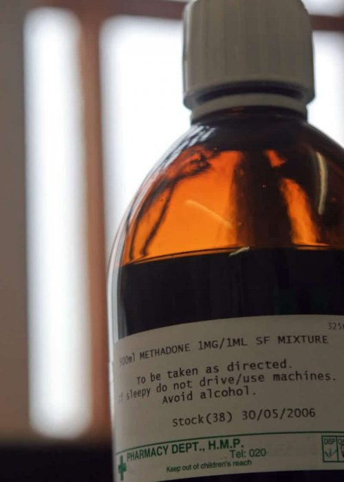 A bottle of Methadone mixture stands on the window sill in front of the bars in the  prison pharmacy.